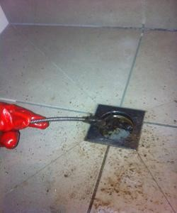 Using had cable machine to clear blocked shower drain